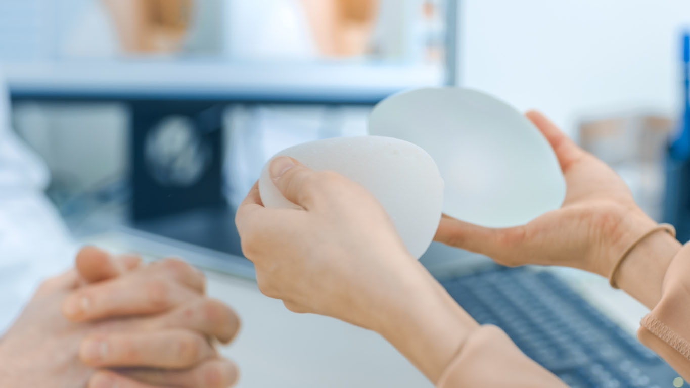 Cosmetic Surgeon Shows Female Patient Breast Implant
